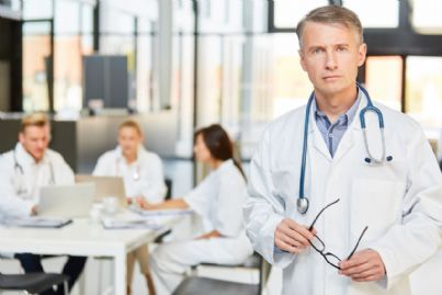 medici seduti a un tavolo e primario in primo piano