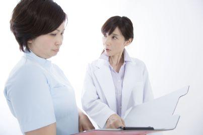 medico donna mostra cartella clinica a infermiera