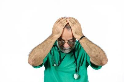 medico con mani in testa per senso di colpa e stetoscopio