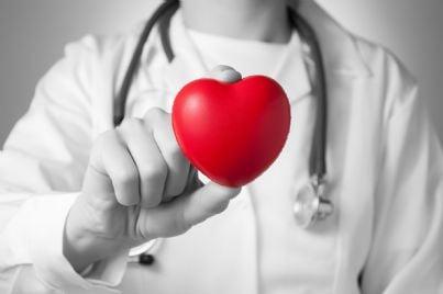 un medico con stetoscopio mostra un cuore