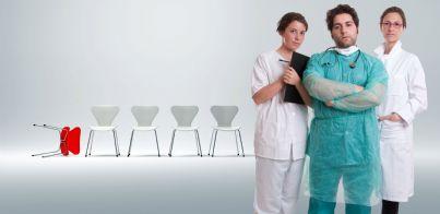 medici seri con file dietro di sedie e una caduta simboleggiante danno