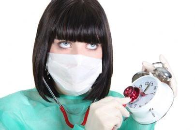 medico donna che mette stetoscopio su sveglia