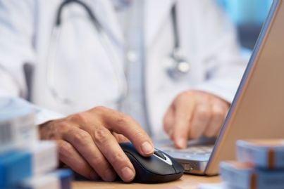 medico che compila ricetta al computer