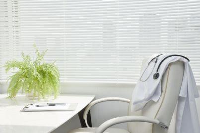 scrivania del medico vuota con camice appoggiato