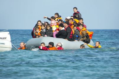 barcone di migranti che ricevono soccorsi in mare