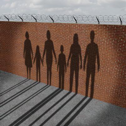 stranieri migranti di fronte a muro con recinzione
