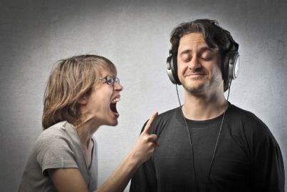 moglie che grida arrabbiata mentre marito ignora ascoltando musica