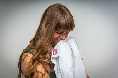 moglie piange tenendo in mano camicia uomo con prova tradimento