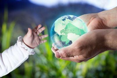 mano di padre che dona al figlio un mondo verde e sostenibile