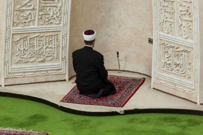 imam che prega di fronte a una moschea