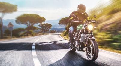 uomo guida moto con luci accese
