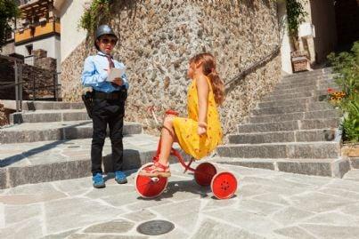 Vicile che fa una contravvenzione a una bambina su triciclo