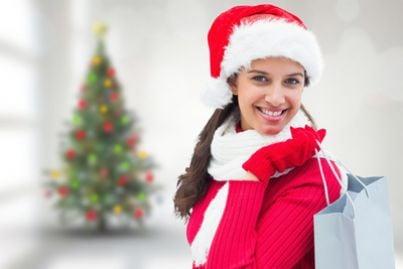 Donna che fa shopping con un albero di natale sullo sfondo