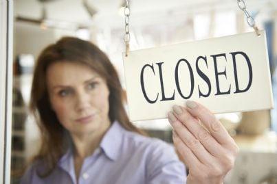 donna che mette cartello negozio chiuso