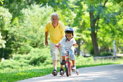 nonno che gioca col nipotino spingendolo in bici