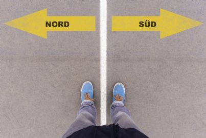 uomo che deve scegliere direzione tra nord e sud