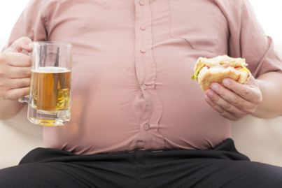 Uomo obeso con panino e birra in mano