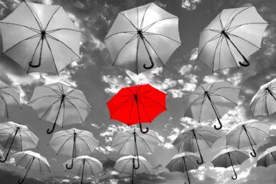 ombrello rosso in mezzo a tanti ombrelli grigi