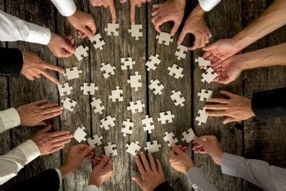 Persone intorno a un tavolo che compongono un puzzle