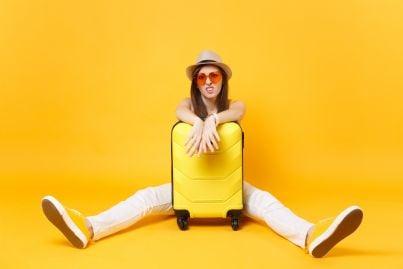 turista con di fronte valigia preoccupata per vacanza rovinata