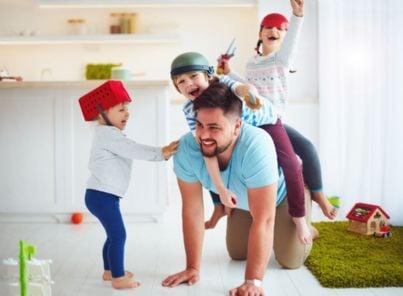 padre gioca con tre figli a casa