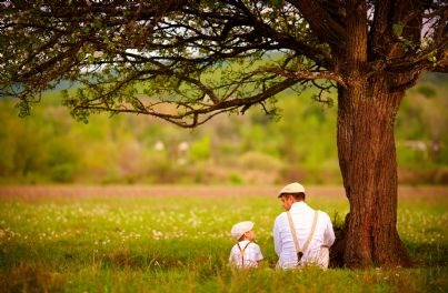 Padre e figlio seduti sotto un albero