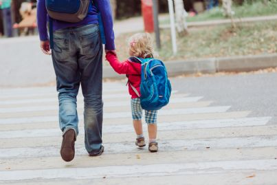 padre porta figlia a scuola con zaino