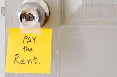 biglietto con invito a pagare affitto affisso alla porta