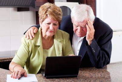 pensionati tristi alle prese con moduli al computer