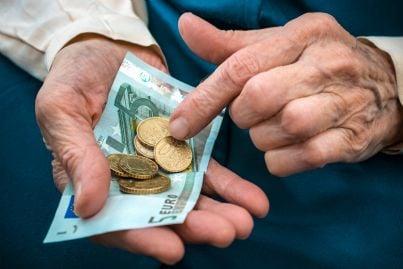 uomo anziano con in mano pochi soldi di pensione