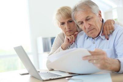 uomo e donna pensionati guardano al computer i propri redditi