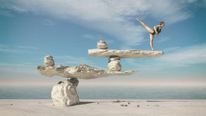 ballerina in equilibrio su pietre in spiaggia