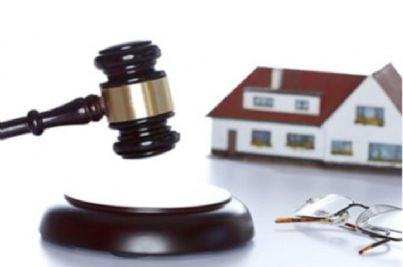 Modello di casa con davanti un martello da magistrato