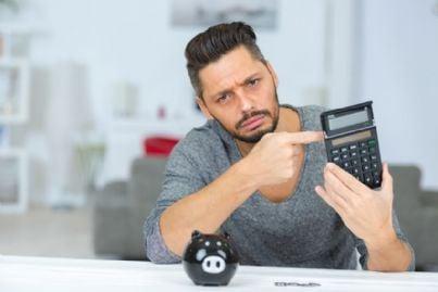 uomo fa i conti con calcolatrice e salvadanaio