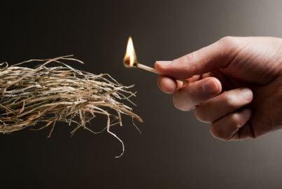 mano di piromane che appicca incendio