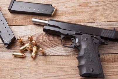 pistola scarica con proiettili a fianco