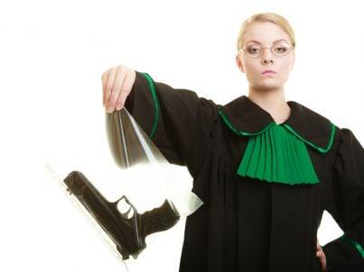 giudice tiene pistola come corpo del reato
