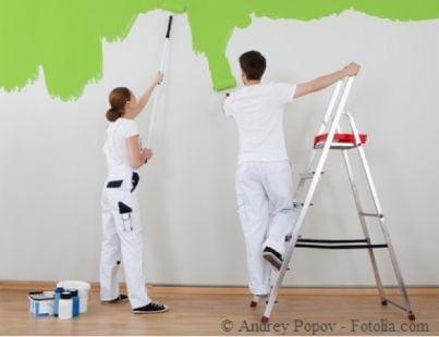 Due lavoratori intenti a tinteggiare un muro
