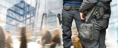 polizia armata con di fronte strada e grattacieli