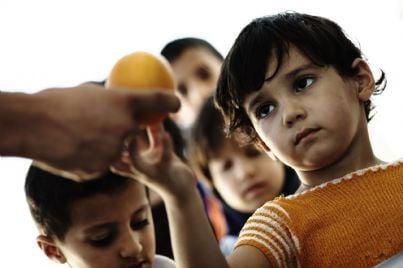bambini poveri in coda per ricevere cibo