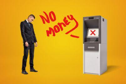 uomo triste di fronte al bancomat che avverte che non ci sono soldi