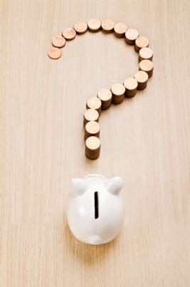un salvadanaio con vicino punto interrogativo fatto di monete