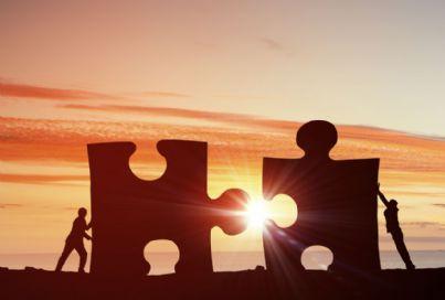 uomini che uniscono due pezzi di un puzzle