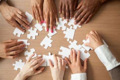 mani che mettono insieme dei pezzi di un puzzle in un lavoro di squadra