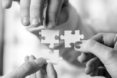 mani che uniscono tessere di un puzzle