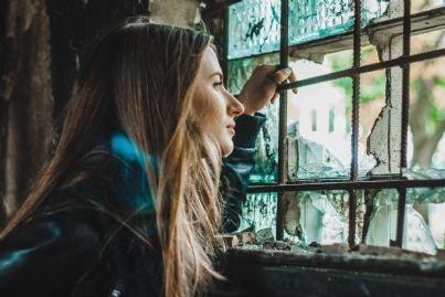 ragazza che guarda attraverso finestra rotta