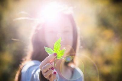 ragazza che mostra una foglia di marijuana