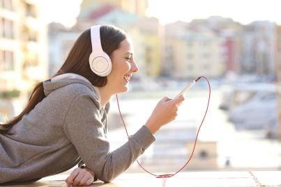 ragazza ascolta musica sul telefono con cuffie