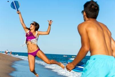 due ragazzi che giocano a racchette sulla spiaggia