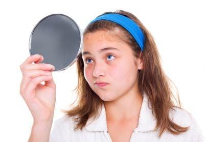 ragazzina che guarda allo specchio in cerca di difetti